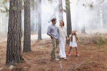 Família feliz andando na floresta — Fotografia de Stock