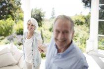 Пожилые супружеские пары Холдинг руки на патио — стоковое фото