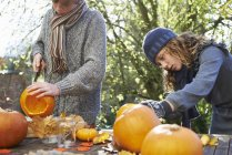 Children carving pumpkins together at outdoor table — Stock Photo