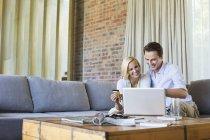 Couple shopping online on sofa — Stock Photo