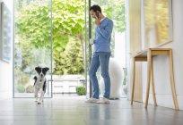 Cão correndo passado homem na cozinha — Fotografia de Stock