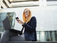 Businesswoman sitting on bench using cell phone — Stock Photo