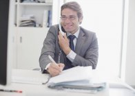 Smiling businessman talking on telephone and writing — Stock Photo