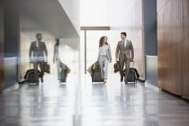 Businessman and businesswoman pulling suitcases through corridor — Stock Photo
