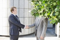 Businessmen shaking hands on city street — Stock Photo