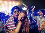 Casal com bastões de brilho abraçando no festival de música — Fotografia de Stock
