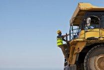 Worker climbing machinery on site — Stock Photo