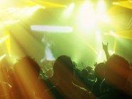 Силуэты болельщики перед освещенной сцене — стоковое фото