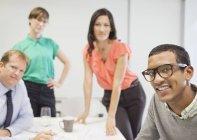 Geschäftsleute, die lächelnd in treffen im modernen Büro — Stockfoto