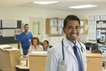 Doctor smiling in modern hospital hallway — Stock Photo