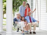 Семья, вместе улыбаясь на крыльце — стоковое фото