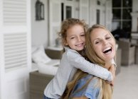 Happy mother and daughter playing on the porch — стоковое фото