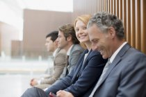 Portrait of smiling businesswoman sitting with businessmen — Stock Photo
