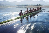 Rowing team rowing scull on lake — Stock Photo