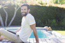 Усміхнений чоловік розслабляючий на дерев'яному майданчику біля басейну — стокове фото