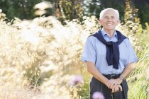 Smiling older man standing outdoors — Stock Photo