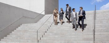 Business people talking and descending urban stairs — Stock Photo