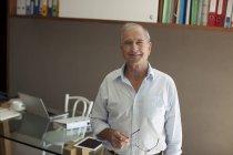 Vieil homme souriant au bureau — Photo de stock
