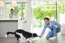 Чоловік грає з собакою кухні в сучасному будинку — стокове фото