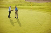Senior men shaking hands on golf course — Stock Photo