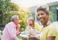 Portrait smiling mature woman enjoying lunch with friends in garden — Stock Photo