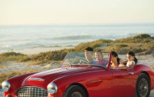 Family in convertible on beach — Stock Photo