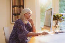 Senior woman working at computer in home office — Stockfoto