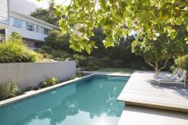 Wooden deck and lounge chairs by swimming pool — Stock Photo