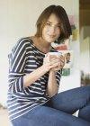 Portrait smiling brunette woman drinking coffee — Stock Photo
