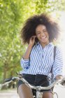 Enthusiastic woman with afro riding bicycle listening to music on headphones — Stock Photo