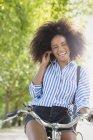 Женщина с мотоциклом слушает музыку в наушниках — стоковое фото