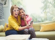 Laughing mature women hugging and taking selfie on sofa — Stockfoto
