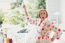 Portrait of playful mature woman in bathrobe dancing in kitchen — Stockfoto