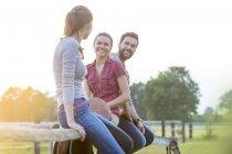 Amici sorridenti seduti sulla recinzione rurale — Foto stock