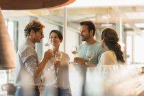 Friends wine tasting white wine in winery tasting room — Stockfoto