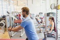Man using cable exercise equipment at gym — Stock Photo