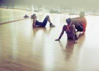 Freunde, Rast- und sprechen auf Studioboden gym — Stockfoto