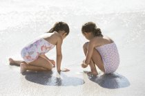 Girls playing together in surf on beach — Stock Photo