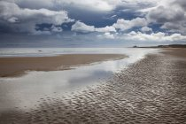Nuvole sopra la spiaggia con la bassa marea — Foto stock