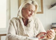 Smiling senior woman in sweater texting with cell phone in kitchen — Stock Photo