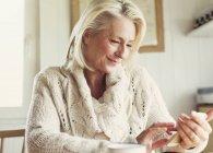 Усміхаючись старший жінка в светр текстові повідомлення з мобільного телефону в кухні — стокове фото