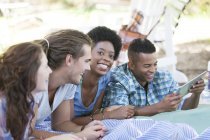 Friends using digital tablet on blanket — Stock Photo