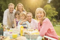 Multi-generation family at table in backyard — Stock Photo