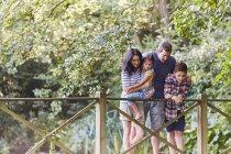 Famiglia che sta sulla passerella in parco con alberi — Foto stock