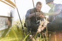 Father and adult son preparing fishing lines — Stock Photo