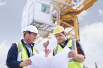 Construction worker and engineer reviewing blueprints below crane at construction site — Stock Photo