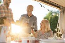 Family drinking wine at sunny patio table — Stockfoto