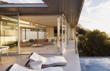 Sillas de salón junto a la piscina de la casa moderna - foto de stock