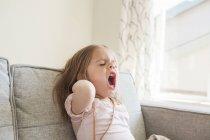 Menina da criança bocejando no sofá — Fotografia de Stock
