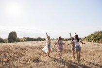 Carefree boho women dancing in sunny rural field — Stock Photo